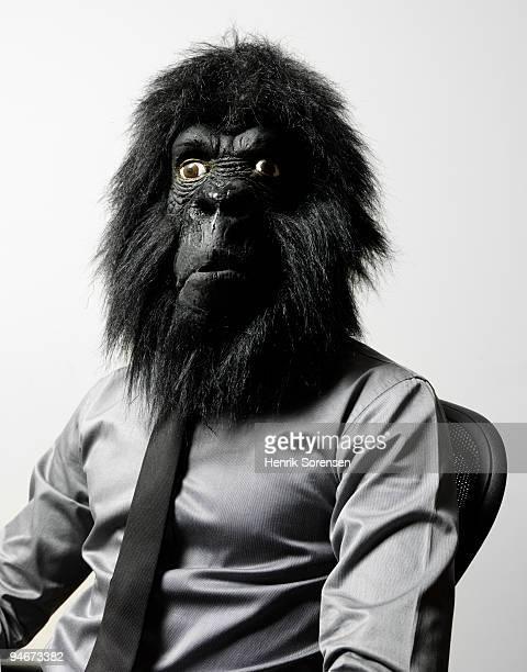Businessman in office chair in gorilla mask