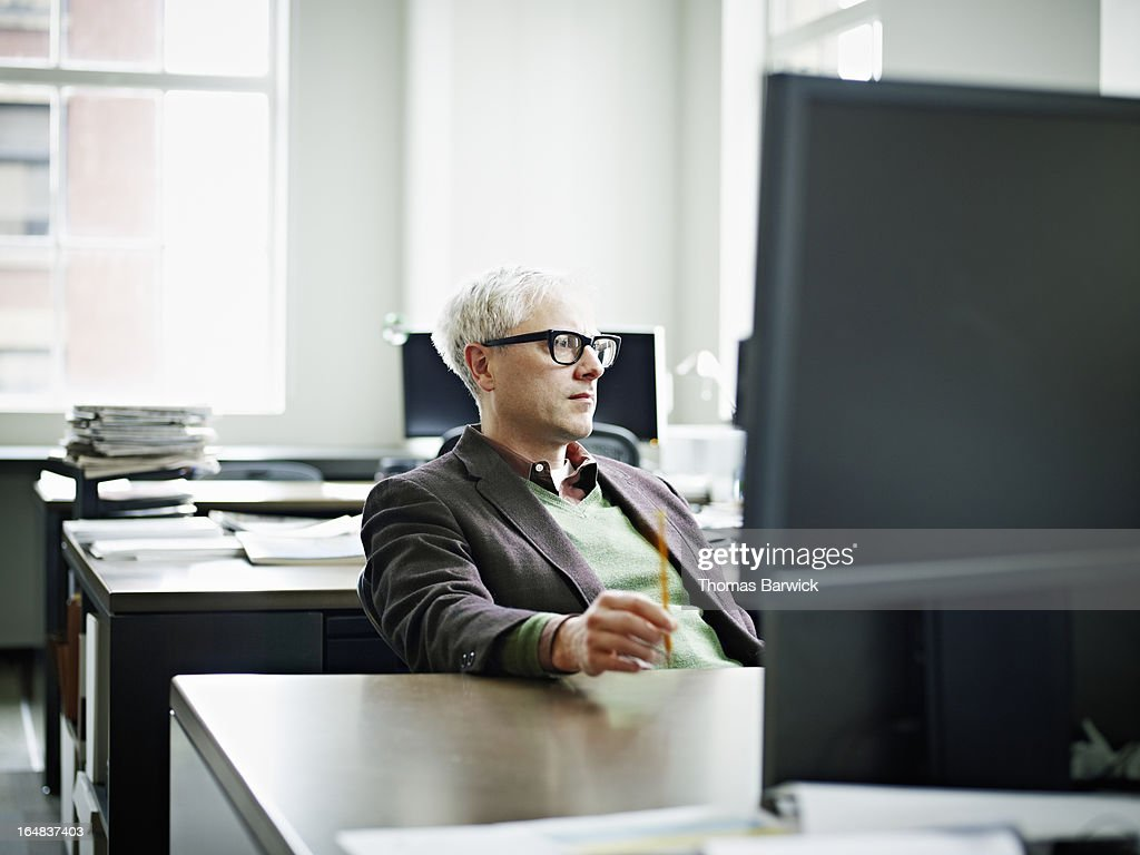 Businessman in office examining computer monitor