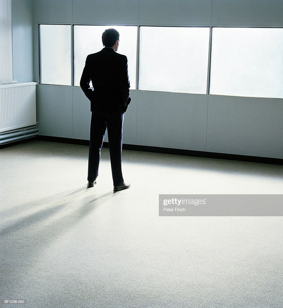 Businessman in office, hands in pockets, rear view : Stock Photo