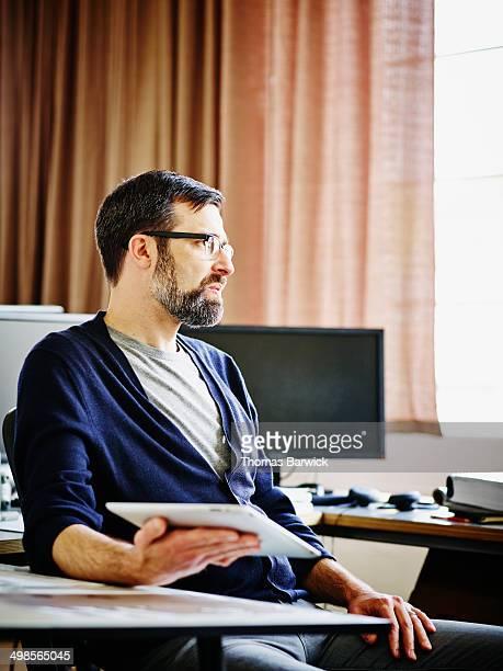 Businessman in office holding digital tablet