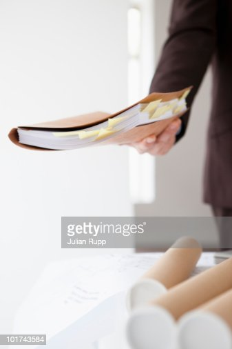 Businessman in office holding documents, mid section : Stock Photo