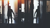 Silhouette of boss or businessman standing in dark office interior with a lot of reflections near meeting rooms and holding katana sword like japanese samurai warrior ready to defense or fight