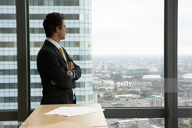 Businessman in office, looking out window, arms crossed, side view