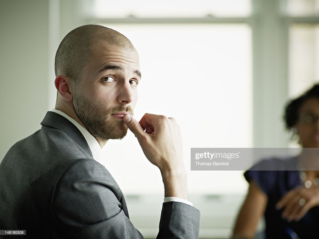 Businessman in office looking over shoulder : Stock Photo