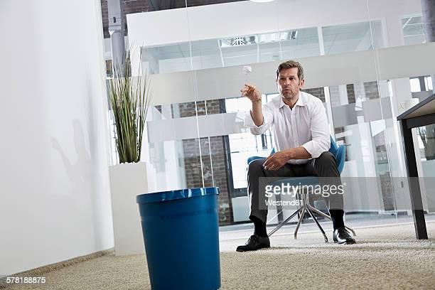 Businessman in office throwing crumpled paper in wastepaper basket