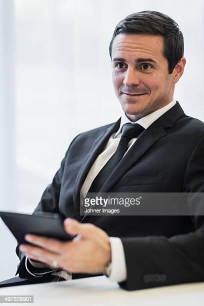Businessman in office using digital tablet, Stockholm, Sweden
