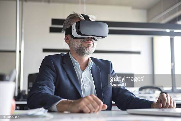 Businessman in office wearing virtual reality glasses