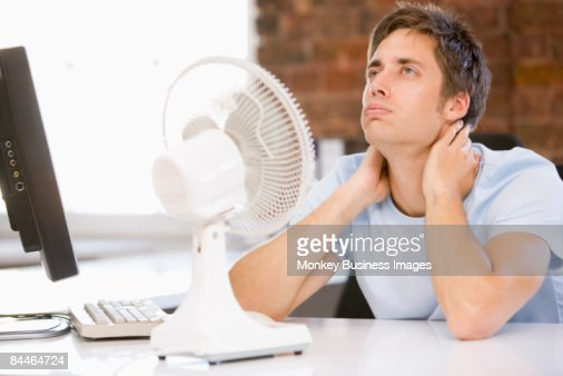 Businessman in office with computer and fan cooling off : Foto de stock