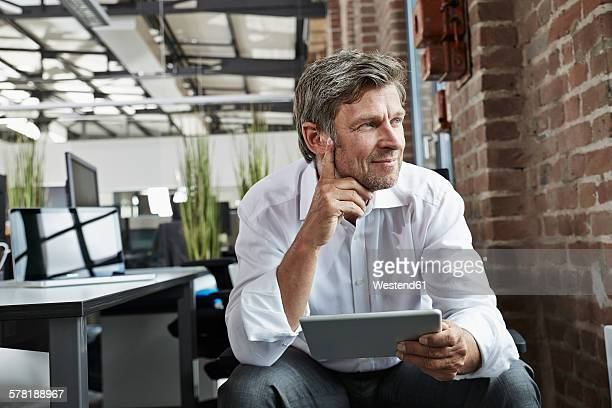 Businessman in office with digital tablet looking to the side