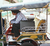 Businessman in open taxi, side view
