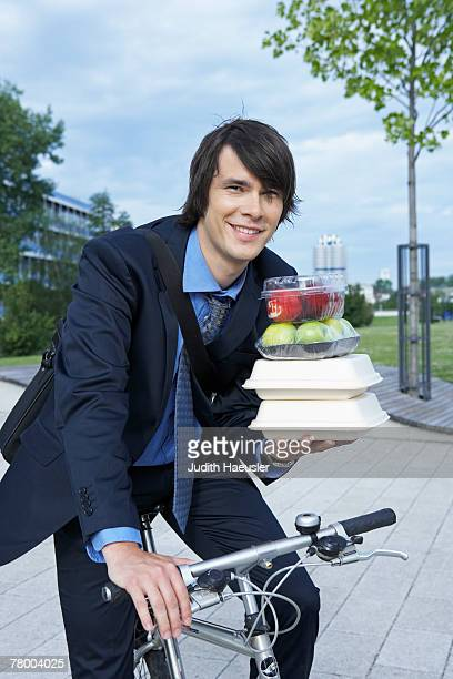Businessman in park on bike with lots of lunchboxes laughing.
