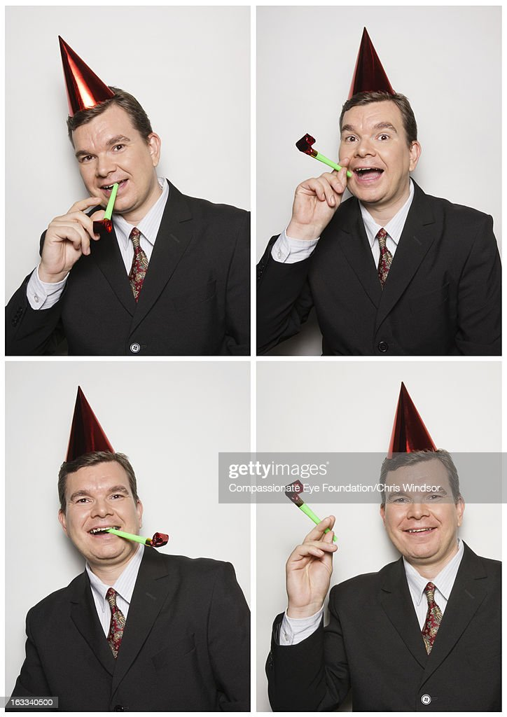 Businessman in photo booth wearing party hat : Stock Photo