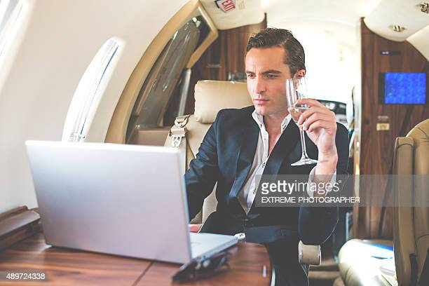 Businessman in private jet drinking champagne