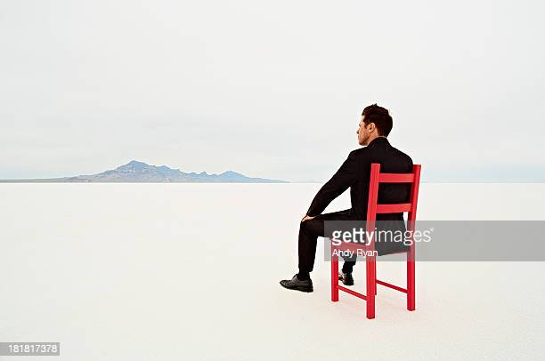Businessman in red chair in desert, facing horizon