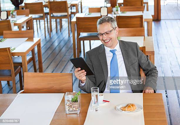 Businessman in restaurant with digital tablet