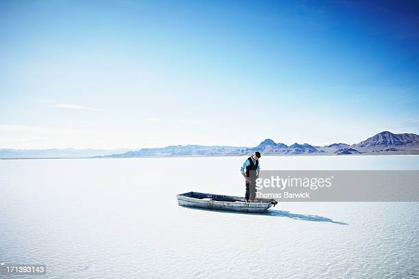 Businessman in small boat on lake looking down