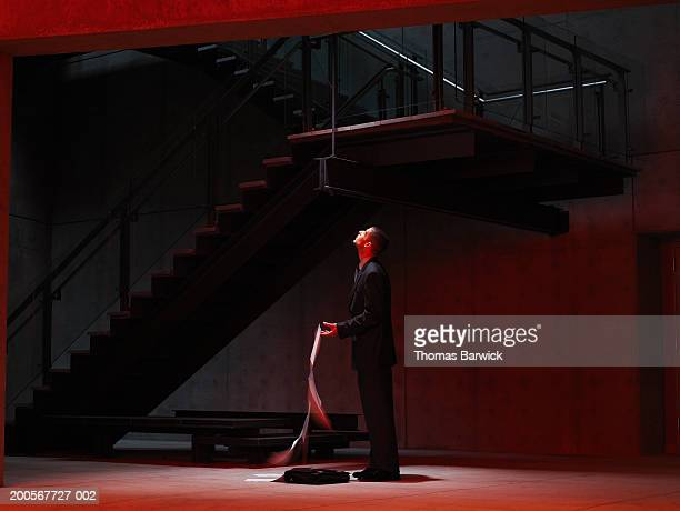 Businessman in stairwell dropping papers, looking up