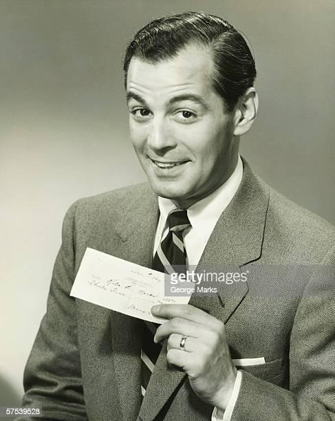 Businessman in studio showing cheque, smiling, (B&W), portrait