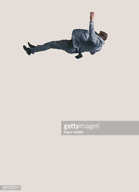 Businessman in suit falling down from high up