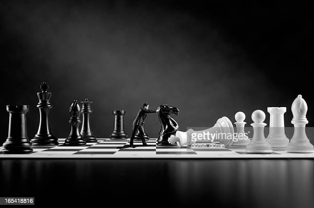 Businessman in suit is pushing black Chess Pieces, Chess board
