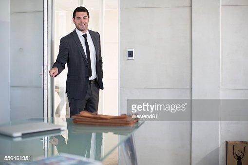 Businessman in suit opening boardroom door