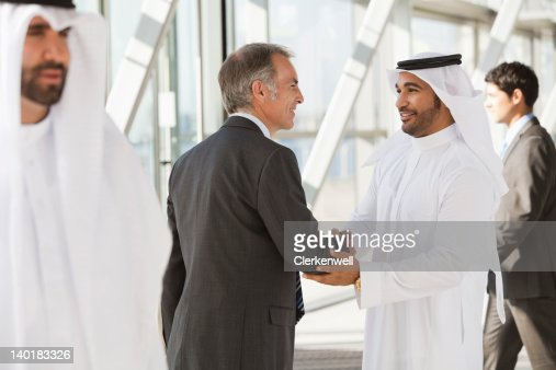 Businessman in suit shaking hands with businessman in kaffiyeh