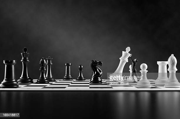 Businessman in suit supporting falling white Chess King, Chess board