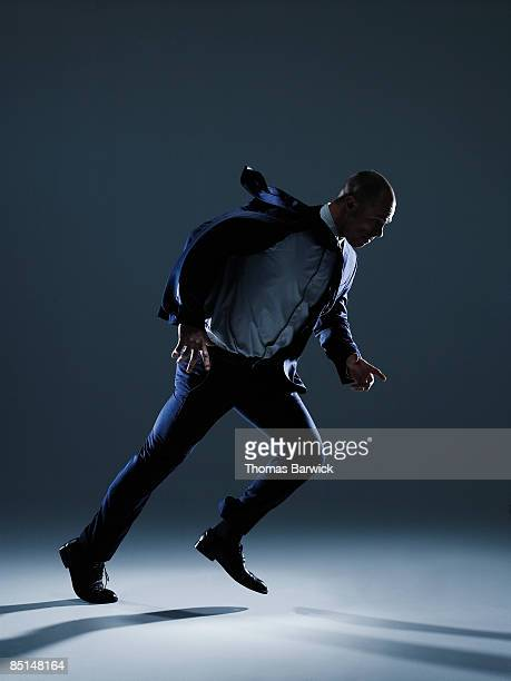 Businessman in suit walking against strong wind