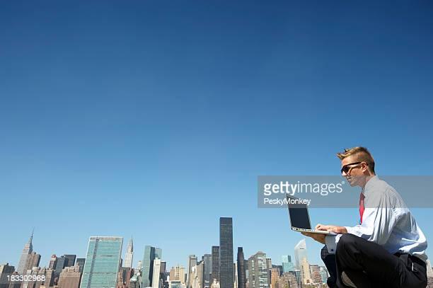 Geschäftsmann in Sonnenbrille Tippen auf Laptop auf die Skyline der Stadt