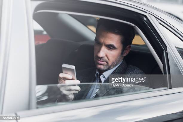 Businessman in the back seat of a car looking at the mobile phone