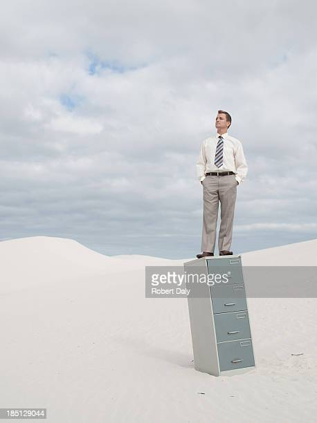 A businessman in the middle of a desert standing on his filing cabinet