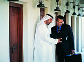 Businessman in Traditional Middle Eastern Dress Showing Another Businessman a Document in a Folder