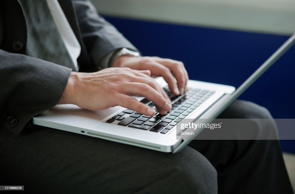 Businessman in train, holding laptop computer