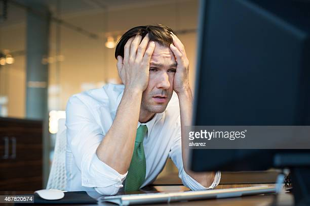Businessman in trouble looking at computer