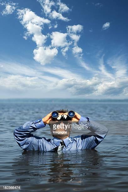 Businessman in water looking through binoculars