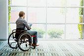 Businessman in wheelchair using digital tablet in office