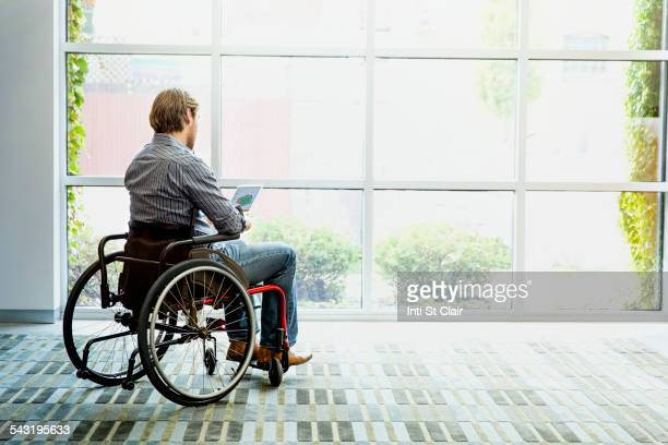 Businessman in wheelchair using digital tablet in office