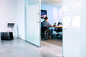 Businessman in wheelchair working at desk in office