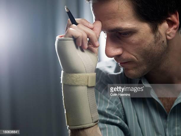 Businessman in wrist brace with pencil