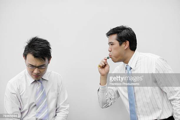 Businessman indoors blowing whistle beside other businessman