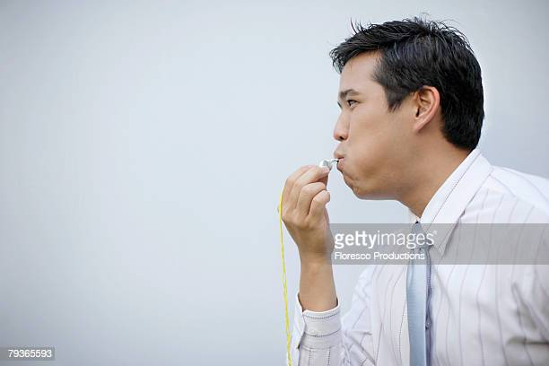 Businessman indoors blowing whistle
