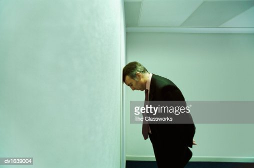 Businessman Indoors With His Head Against a Wall : Stock Photo