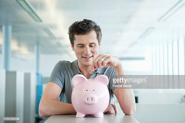 Businessman inserting a coin into a piggy bank