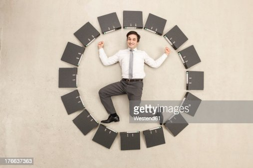 Businessman inside circle of files forming clock