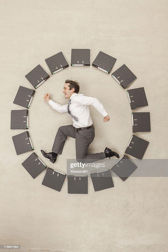 Businessman inside circle of files forming clock : Foto de stock