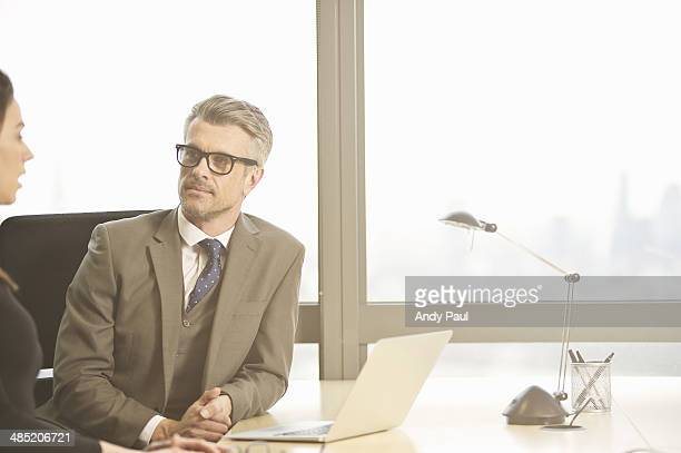 Businessman interviewing young female candidate in office