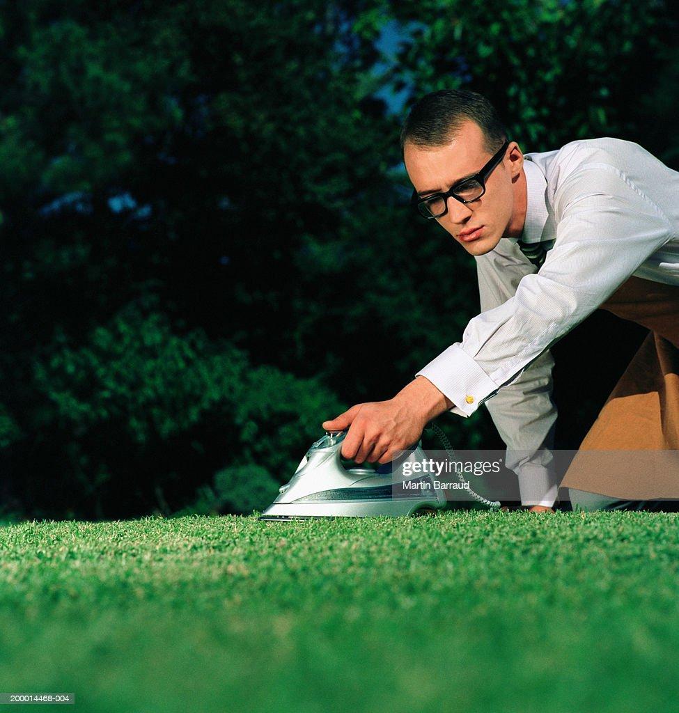 Businessman ironing lawn, close-up