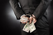 Businessman is arrested and handcuffed with dollar high quality and high resolution studio shoot