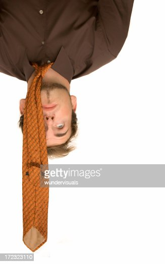 Businessman is hanging upside down having stress