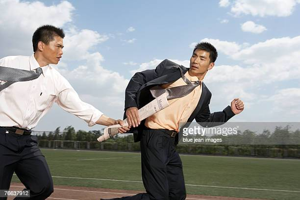 A businessman is passing a piece of news to another businessman.
